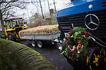 © Joel Goodman - 07973 332324 . 6 December 2013 . Marple , UK . A Unimog is used to tow a carrier in which friends and family were transported from the pub to the church . The funeral of farmer Bob Watson . His son David Watson drives his father's coffin on a trailer hooked to the back of Bob's favourite tractor through Marple via Bob's local pub before taking it on to the church . Photo credit : Joel Goodman