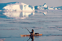 Inuit hunter in a skin Kayak on ice free summer seas, waits for a seal to surface. Qeqertat. Thule. Greenland.
