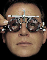MODEL RELEASED. Eye examination. Man looksthrough a set of lenses during an ophthalmicexamination of his eyes. The ophthalmologist isadjusting the lenses as the patient looks at awall chart (not seen). The ability to read thechart guides the ophthalmologist in choosinglenses to correct the patientandamp;apos;s sight.