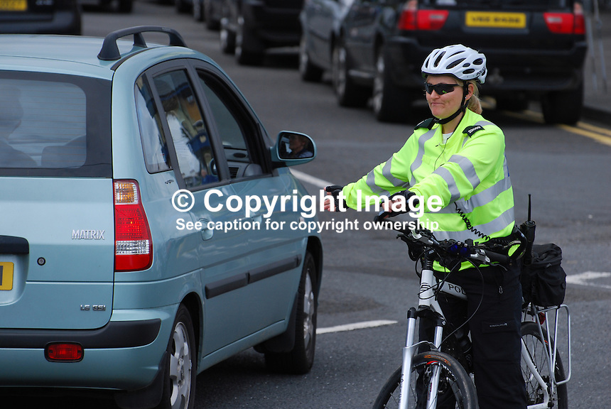 Policewoman, on bike patrol, directs traffic in Holywood, Co Down, N Ireland, UK. 200908162985..Copyright Image from Victor Patterson, 54 Dorchester Park, Belfast, UK, BT9 6RJ..Tel: +44 28 9066 1296.Mob: +44 7802 353836.Voicemail +44 20 8816 7153.Skype: victorpattersonbelfast.Email: victorpatterson@mac.com.Email: victorpatterson@ireland.com (back-up)..IMPORTANT: If you wish to use this image or any other of my images please go to www.victorpatterson.com and click on the Terms & Conditions. Then contact me by email or phone with the reference number(s) of the image(s) concerned.