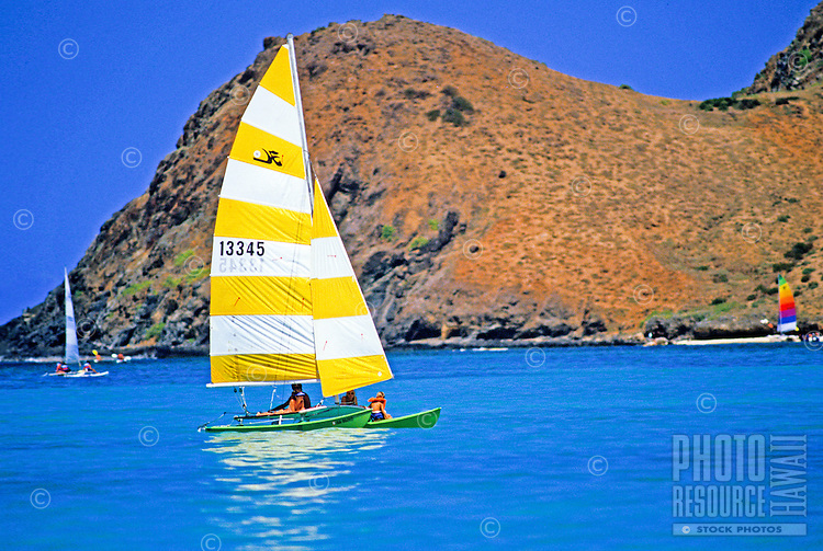 Catamaran with yellow & white sail in blue waters off Lanikai.