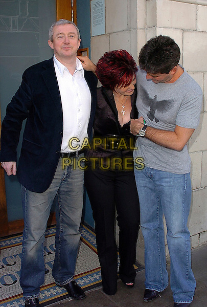 LOUIS WALSH, SHARON OSBOURNE & SIMON COWELL.The X Factor II - press launch at The Electric Cinema, W10..August 15th, 2005.full length grey gray t-shirt t shirt jeans denim gesture cleavage funny.www.capitalpictures.com.sales@capitalpictures.com.©Capital Pictures