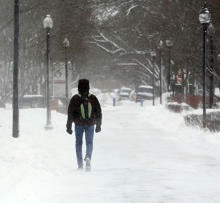 A pedestrian makes his way through the blustery quad at the Lincoln Park campus of DePaul University in Chicago as the New Year brought two days of lake effect snow and ice. (Photo by Jamie Moncrief)