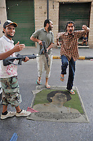Men hold guns and dance on a sheet with Gaddafi's face on it. After a six month revolution, rebel forces finally managed to break into Tripoli and have taken control of Bab al-Aziziyah, Col Gaddafi's compound and residence. Few remain that are loyal to Gaddafi in the city; it is seeming that the 42 year regime has come to an end. Gaddafi is currently on the run.