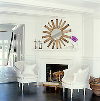 The large circular mirror above the living room fireplace was made from the slats of a wine-barrel and the pair of matching armchairs and small footstool are antique shop finds