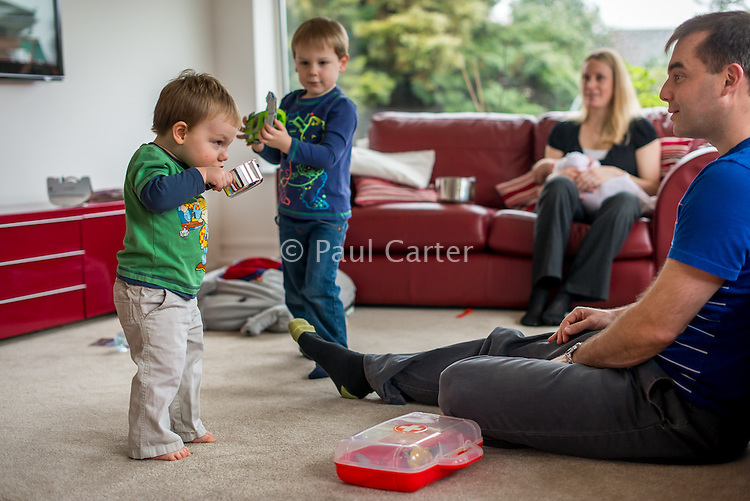 A woman sitting on her living room sofa and breastfeeding her 2 month old baby daughter while her two older boys play with their father .<br /> <br /> Hampshire, England, UK<br /> 10/02/2013