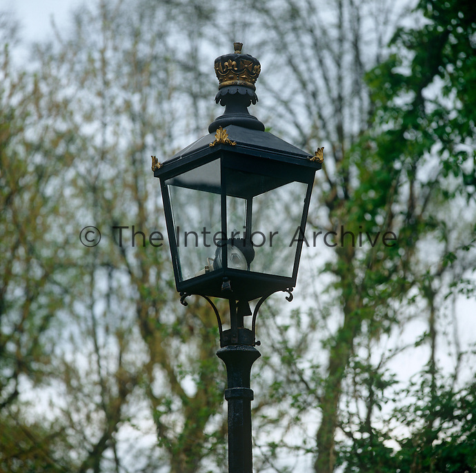 An old-fashioned lamp post decorated with a ducal crown stands in the grounds of the house which is situated in secluded corner of the Bois de Boulogne in Paris
