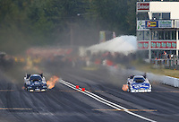 Aug. 2, 2014; Kent, WA, USA; NHRA funny car driver Alexis DeJoria (left) races alongside Tommy Johnson Jr during qualifying for the Northwest Nationals at Pacific Raceways. Mandatory Credit: Mark J. Rebilas-