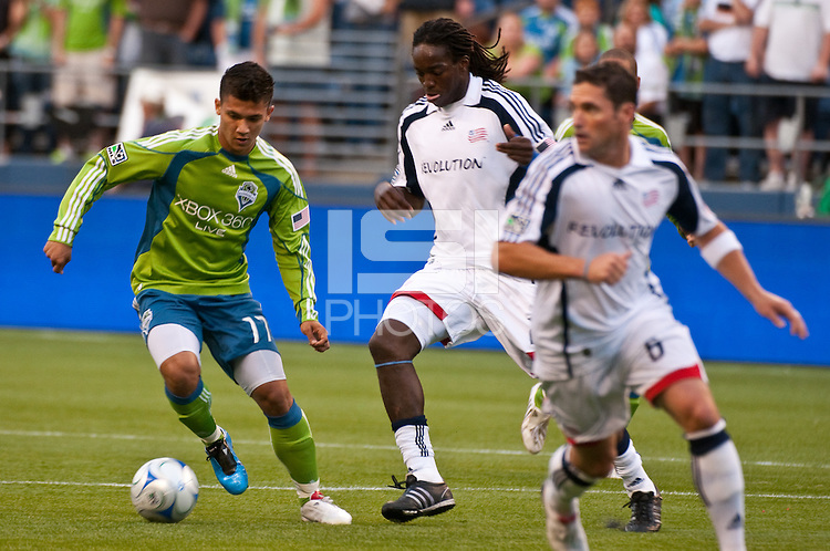 Fredy Montero (17) of the Seattle Sounders drives against Shalrie Joseph (c) and Jay Heaps (r) of the New England Revolution in the match at the XBox Pitch at Quest Field on August 20, 2009. The Revolution defeated the Sounders 1-0.