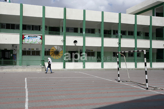 A Palestinian school girl walks at her a closed school during a strike of the employees of former Palestinian government in Gaza Strip to demand for pay their salaries, in Rafah in the southern Gaza strip, on Oct. 15, 2014. Photo by Abed Rahim Khatib