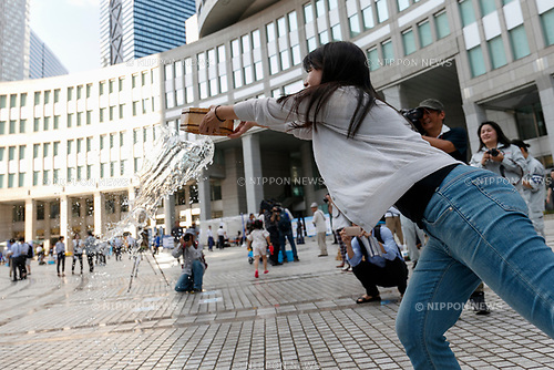 A woman enjoys sprinkling water during the Uchimizu-Biyori event outside the Tokyo Metropolitan Building on July 20, 2017, Tokyo, Japan. Uchimizu is a Japanese summer tradition of wetting down the streets by sprinkling water to keep down dust and cool pavements to reduce the temperature. (Photo by Rodrigo Reyes Marin/AFLO)
