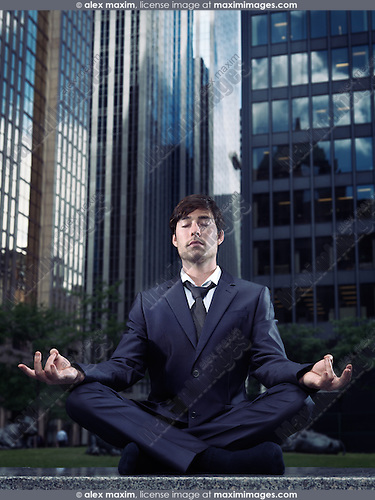 Conceptual portrait of a businessman wearing a suit sitting crosslegged meditating outdoors with downtown office buildings in the background. Meditation and busy urban lifestyle concept. Toronto, Canada.
