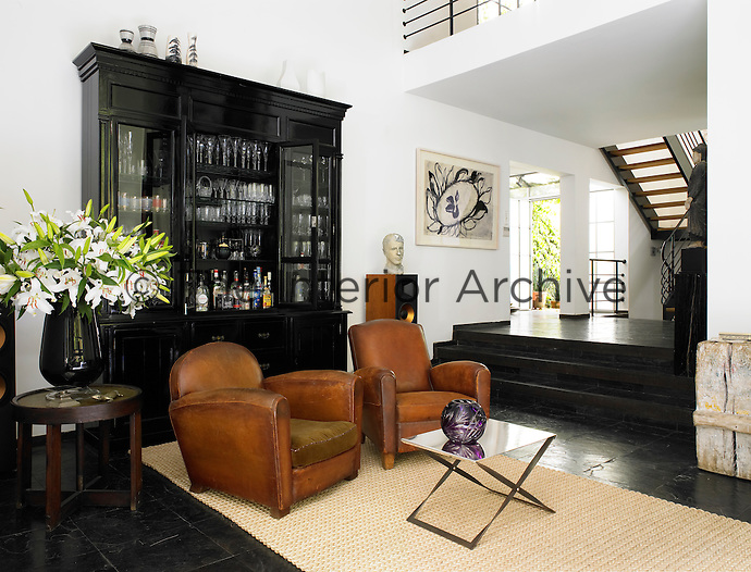 Steps lead down to a drawing room area with a tiled floor. Two leather armchairs stand in front of a display cabinet holding drinks and glassware.