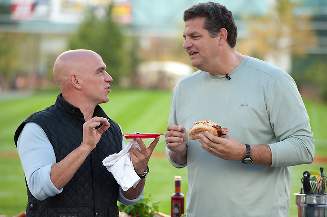 """October  14, 2011 - Bristol, CT - Campus Green: ABC's """"The Chew"""" Chef Michael Symon with Mike and Mike in the Morning's Mike Golic.  . .Credit: Joe Faraoni"""