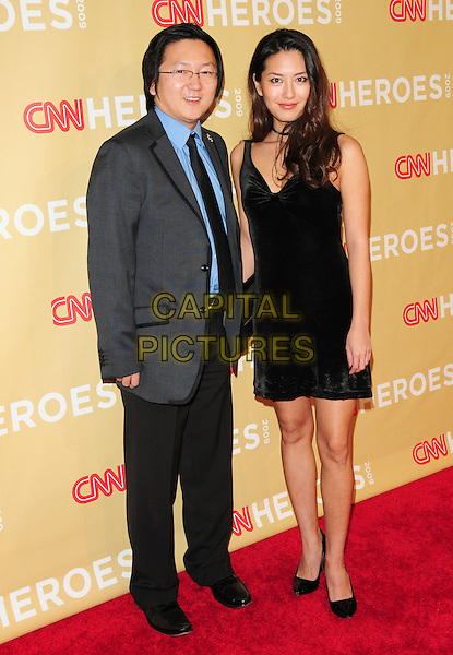 MASI OKA & GUEST .at The 3rd Annual CNN Heroes: An All-Star Tribute held at The Kodak Theatre in Hollywood, California, USA,  November 21st 2009                                                                   .full length grey gray jacket black trouser blue shirt tie dress velvet .CAP/RKE/DVS.©DVS/RockinExposures/Capital Pictures