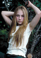 Adolescent girl with long blonde hair in moody pose. Mara. Massachusetts.