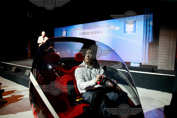 An engineer steers a concept en-v electric vehicle while Dan Akerson, chief executive officer of General Motors Co. (GM), makes a presentation.