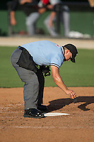 Home plate umpire Cody Clark cleans off the plate during the South Atlantic League game between the Hickory Crawdads and the Kannapolis Intimidators at CMC-Northeast Stadium on May 21, 2015 in Kannapolis, North Carolina.  The Intimidators defeated the Crawdads 2-0 in game one of a double-header.  (Brian Westerholt/Four Seam Images)