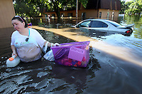 Kristi Elliott of Ames wades through waist-deep flood water while salvaging some of her belongings from her apartment on South 5th St. in Ames Wednesday morning.  Flooding in Ames, Iowa Wednesday, August 11, 2010 from the flooded South Skunk River and Squaw Creek.