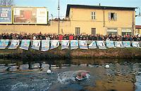"""Milano, Cimento Invernale. I canottieri del Club Canottieri Olona al quartiere S. Cristoforo sfidano le acque gelide del Naviglio Grande attraversando a nuoto il canale da una sponda all'altra durante i """"giorni della merla"""", considerati i giorni più freddi dell'inverno. L'evento attira centinaia di persone assumendo quasi il carattere di festa popolare --- Milan, """"Cimento Invernale"""" (winter trial). Rowers of the """"Club Canottieri Olona"""" in S. Cristoforo district challenge the ice cold water of the Naviglio Grande channel by swimming from one bank to the other during the coldest days of winter (""""giorni della merla""""). The event attracts hundreds of people, becoming so a sort of popular meeting"""