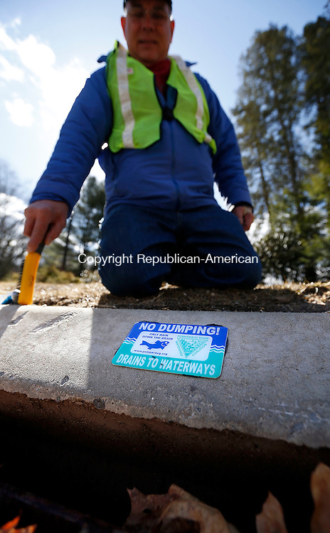 Woodbury, CT- 11 April 2015-041115CM02-  David Mechler of Woodbury places a no dumping sign on a storm drain along Transylvania Road in Woodbury on Saturday morning.  Mechler was helping clean up areas of the town, which was part of Conservation Commission  biannual town wide cleanup.  Christopher Massa Republican-American