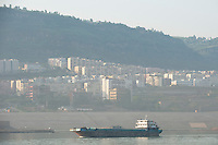 Daytime landscape view of a commercial river freighter on the Cháng Jiāng with commercial buildings in the background in the Wànzhōu District in the Chongqing Municipality.  © LAN