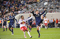 Chris Tierney (8) of the New England Revolution clears the ball away from Dane Richards (19) of the New York Red Bulls during a Major League Soccer (MLS) match at Red Bull Arena in Harrison, NJ, on October 21, 2010.