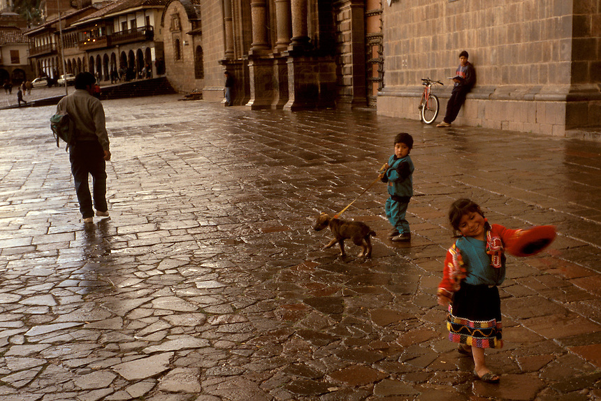 A young girl in traditional Indian dress dances through Cuzco's Plaza de las Armas as her brother hangs onto the family dog at rear. The kids were put on display for their mother to attract alms from passers-by.