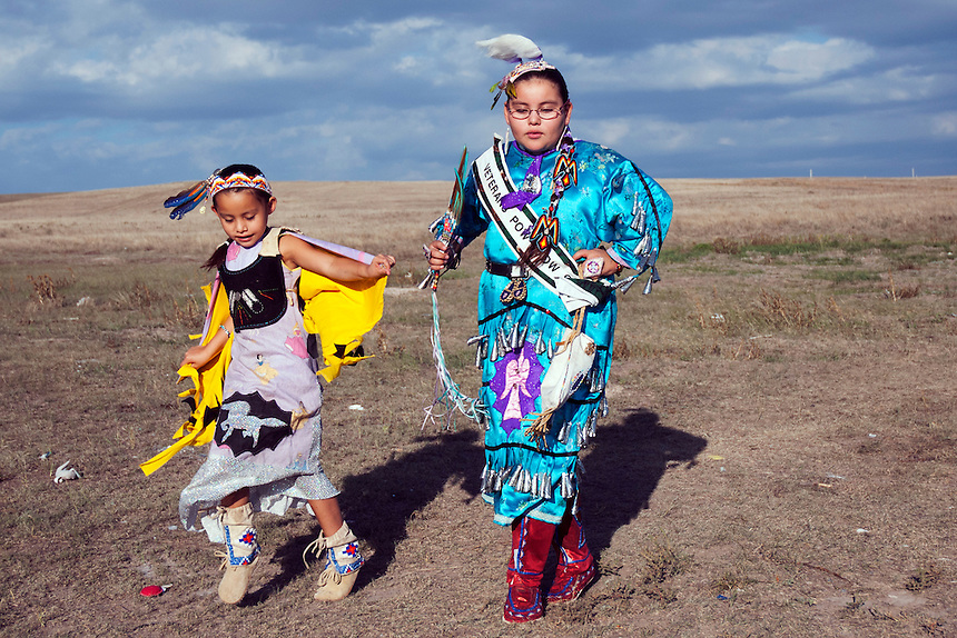 Rhiannon Frazier and her sister, Michel playing on the fields next to their trailer. The girls, grand grand daughters of Chief Red Cloud  are dressed with national costumes hand made by their mother. Their mother, like many others, is unemployed and makes her living selling jewelry she makes from porcupine quills. Unemployment on the Reservation exceeds 78% and 97% of families live below the Federal poverty level. Rhiannon has participated in the regionalveteran Pow Wow for 5 years and has won 17 trophies. In 2007 she has been chosen as the Veteran's Pow Wow queen.