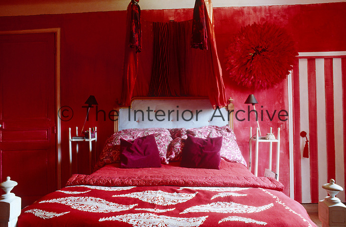 The bright scarlet colour scheme of this bedroom is toned down by accents of white in the padded headboard, the striped door to the bathroom and the embroidered motifs of the bed cover