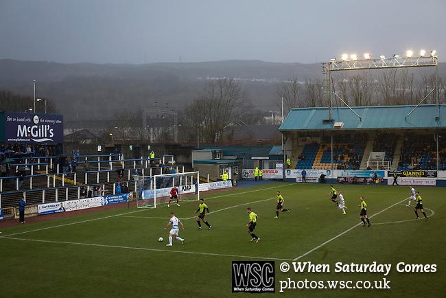 Greenock Morton 2 Stranraer 0, 21/02/2015. Cappielow Park, Greenock. Rain pouring down on home supporters as Greenock Morton (in hoops) take on Stranraer in a Scottish League One match at Cappielow Park, Greenock. The match was between the top two teams in Scotland's third tier, with Morton winning by two goals to nil. The attendance was 1,921, above average for Morton's games during the 2014-15 season so far. Photo by Colin McPherson.