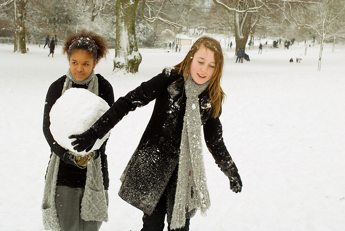 Two friends play in the snow in Queen's Park, Brighton on a 'snow day'.