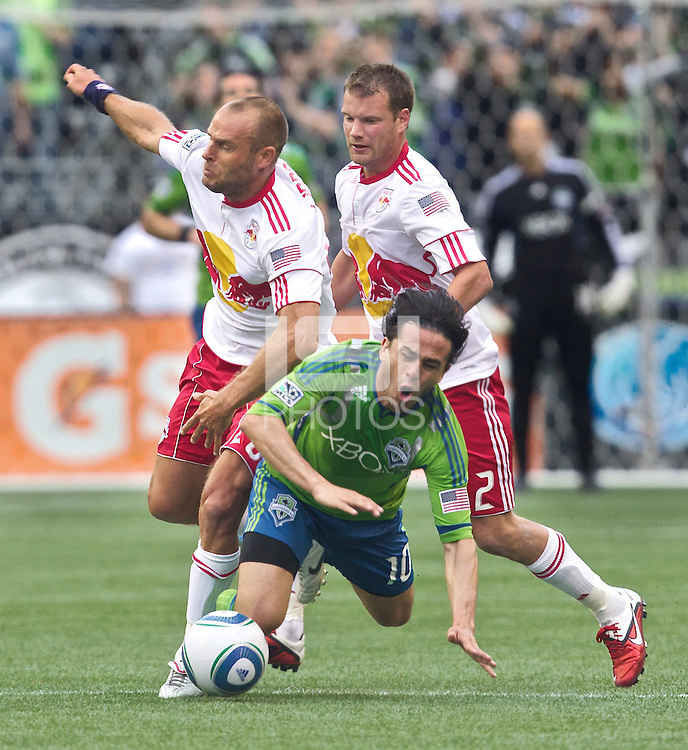 Seattle Sounders FC midfielder Mauro Rosales goes to the ground after colliding with midfielders Joel Lindpere and Teemu Tainio during play at Qwest Field in Seattle Saturday June 23, 2011. The Sounders won the game 4-2.