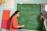 Education high school male math teacher explaining problem to male student at chalkboard