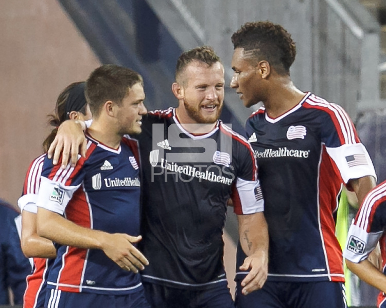 New England Revolution midfielder Kelyn Rowe (11) celebrates his goal with teammates.  In a Major League Soccer (MLS) match, the New England Revolution (dark blue) defeated Philadelphia Union (light blue), 5-1, at Gillette Stadium on August 25, 2013.