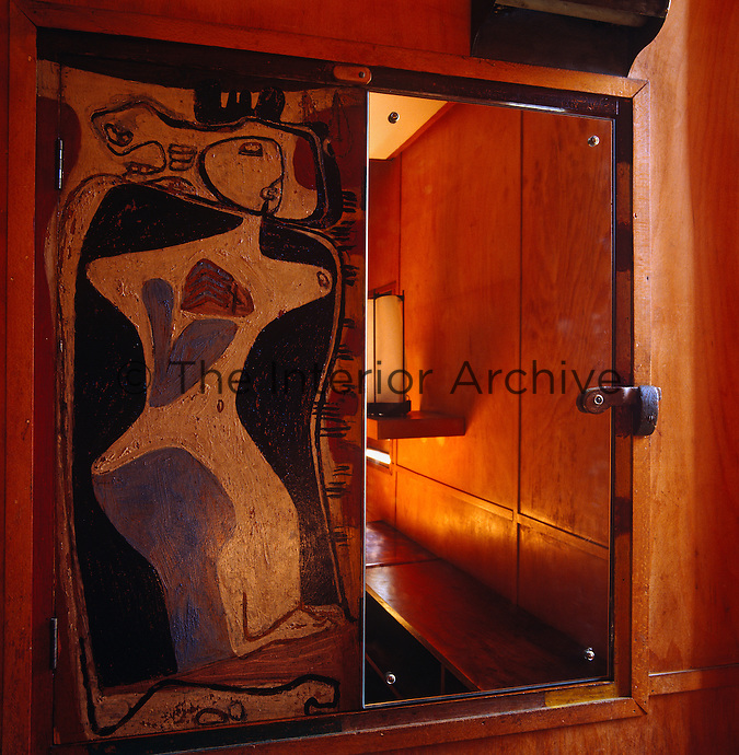 A fresco by Le Corbusier representing the female form has been painted onto one half of a cupboard door while a mirror has been attached to the other