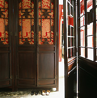 A carved Chinese screen in the main living area is incorporated into an internal door