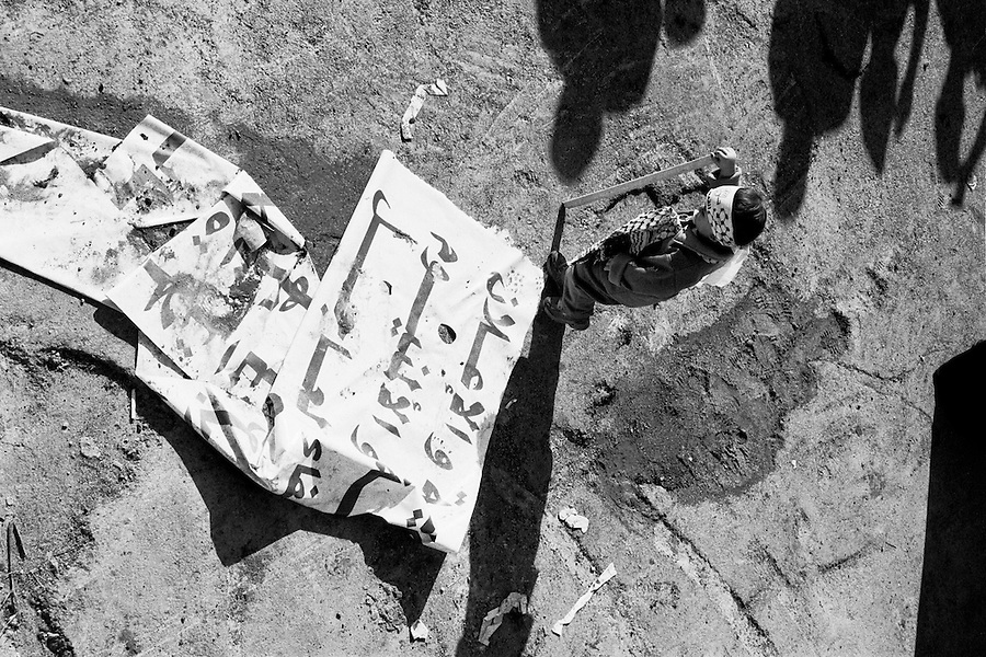 Child standing next to fallen banner at the Muqata presidential compound the day of Yasser Arafat's funeral.