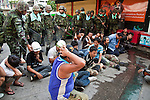 14 MAY 2010 - BANGKOK, THAILAND: Protesters sit on the ground after being arrested by Thai soldiers during a battle on Rama IV Road in Bangkok Friday afternoon. Thai troops and anti government protesters clashed on Rama IV Road Friday afternoon in a series of running battles. Troops fired into the air and at protesters after protesters attacked the troops with rocket and small homemade explosives. Unlike similar confrontations in Bangkok, these protesters were not Red Shirts. Most of the protesters were residents of nearby Khlong Toei slum area, Bangkok's largest slum area. The running battle went on for at least two hours.   PHOTO BY JACK KURTZ