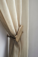 A neutral curtain is held back by a brass tie back.