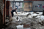 Following weeks of cold and snow, a man clears water from in front of his home in the Krivac Roma Settlement--one of the largest Roma neighborhoods in the region--in Smederevo, Serbia.