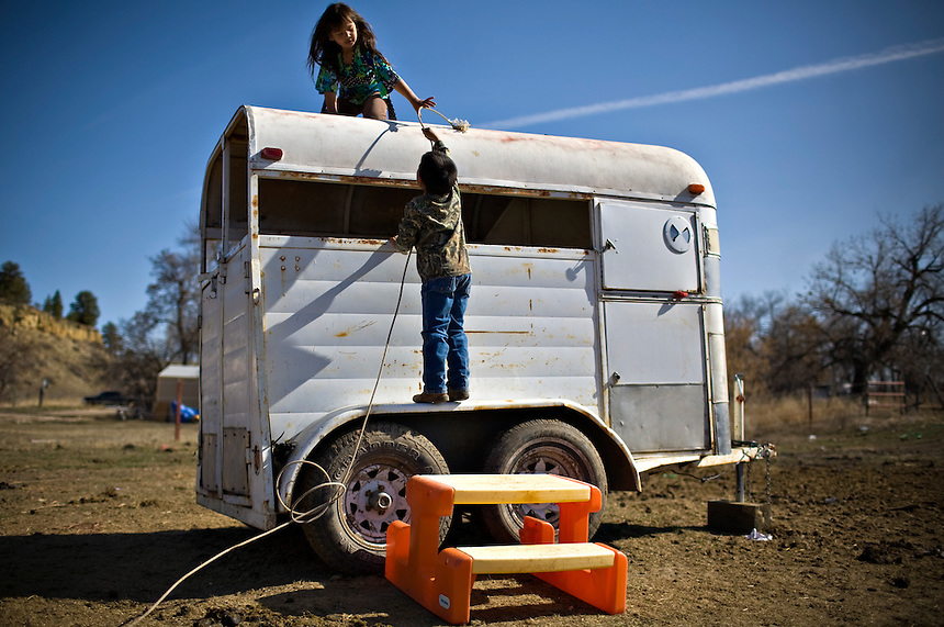 Regis Hogan Jr., 5, plays with his cousin on his family's land outside of Lodge Grass, MT on the Crow Indian Reservation.