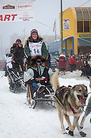 Paige Drobny and team leave the ceremonial start line at 4th Avenue and D street in downtown Anchorage during the 2013 Iditarod race. Photo by Jim R. Kohl/IditarodPhotos.com