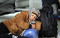 Pictured: A woman, exhausted by the long journey rests at the passenger station Monday 08 Fabruary 2016<br /> Re: Migrants wait in the Piraeus passenger station to be transported to the migrants' camp in Elliniko, Athens, Greece