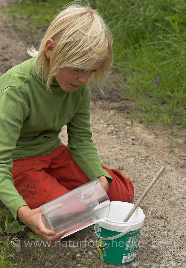 Kinder gießen Tierspur aus Gips, Junge hat Wasser abgemessen und füllt dieses zum Gipsanrühren in alten Becher