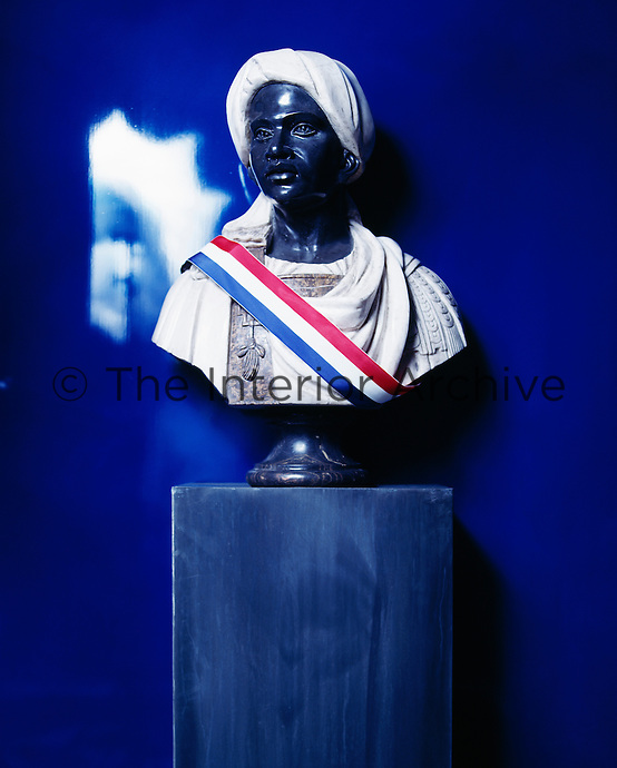The vibrant gallery hall features lacquered blue walls. A bust statue stands on a plinth.