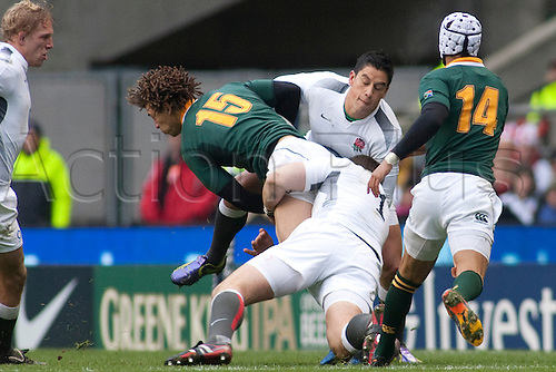 TWICKENHAM LONDON, 27-11-2010.  South Africa's Zane Kirchner, is tackled by England's Andrew Sheridan and England's Shontayne Hape,  during the Investec International match between England and South Africa at Twickenham Stadium Middlesex England.
