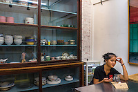 A girl has a drink in front of a cabinet of traditional kitchenware in DR.inc  cafe and Nala Designs in Bangsar, Kuala Lumpur, Malaysia, on 18 August 2015. Nala Designs, by founder and designer Lisette Scheers, is inspired by Malaysia's melting pot of Chinese, Malay and Indian cultures. Photo by Suzanne Lee for Monocle