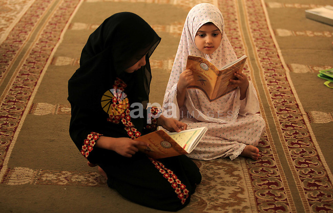 Palestinian girls read verses from the Quran during a class on how to read Islam's holy book, at Dar Al Ketab and sunna in Gaza city, on June 15, 2015. A summer camp in the Gaza Strip, Dar Al Ketab and sunna, plans to teach students the Holy Quran during the summer months inside mosques throughout the Gaza Strip. Photo by Ashraf Amra