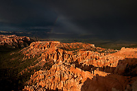 730750184 summer monsoon rainstorm and ominous clouds with a rainbow over the hoodoos from bryce point in bryce canyon national park  utah united states